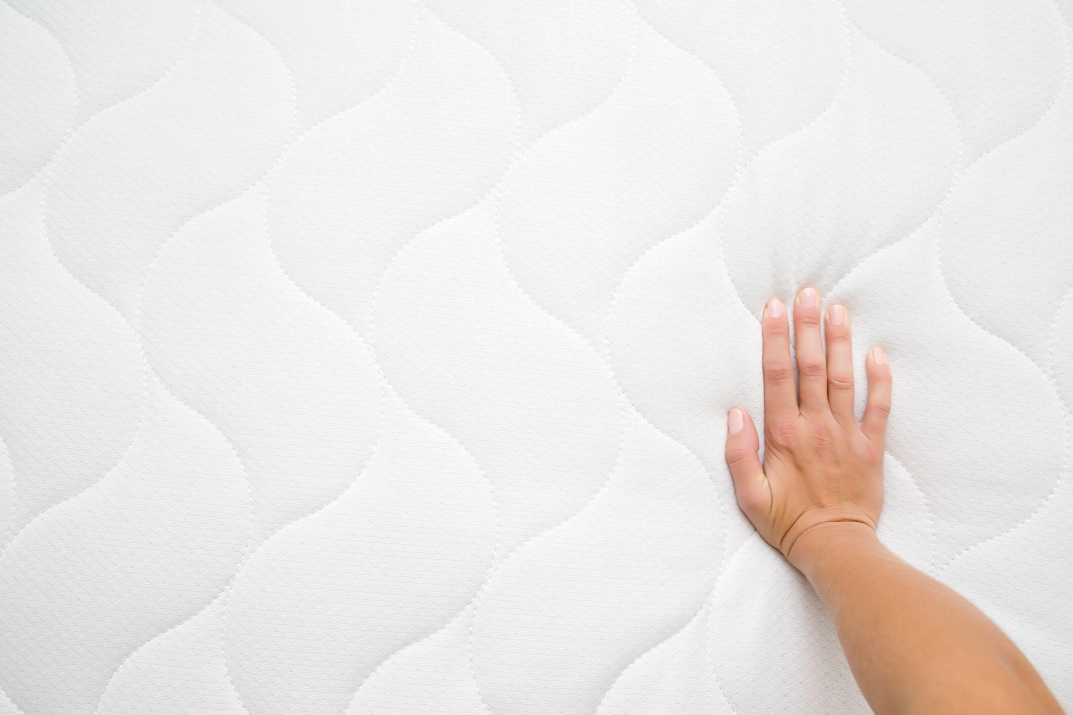 Hand op een wit matras