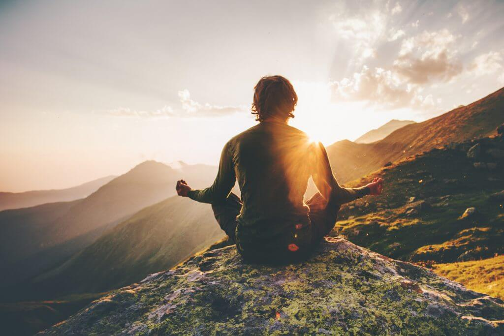 Mediteren voor het slapen op een berg met zonsondergang