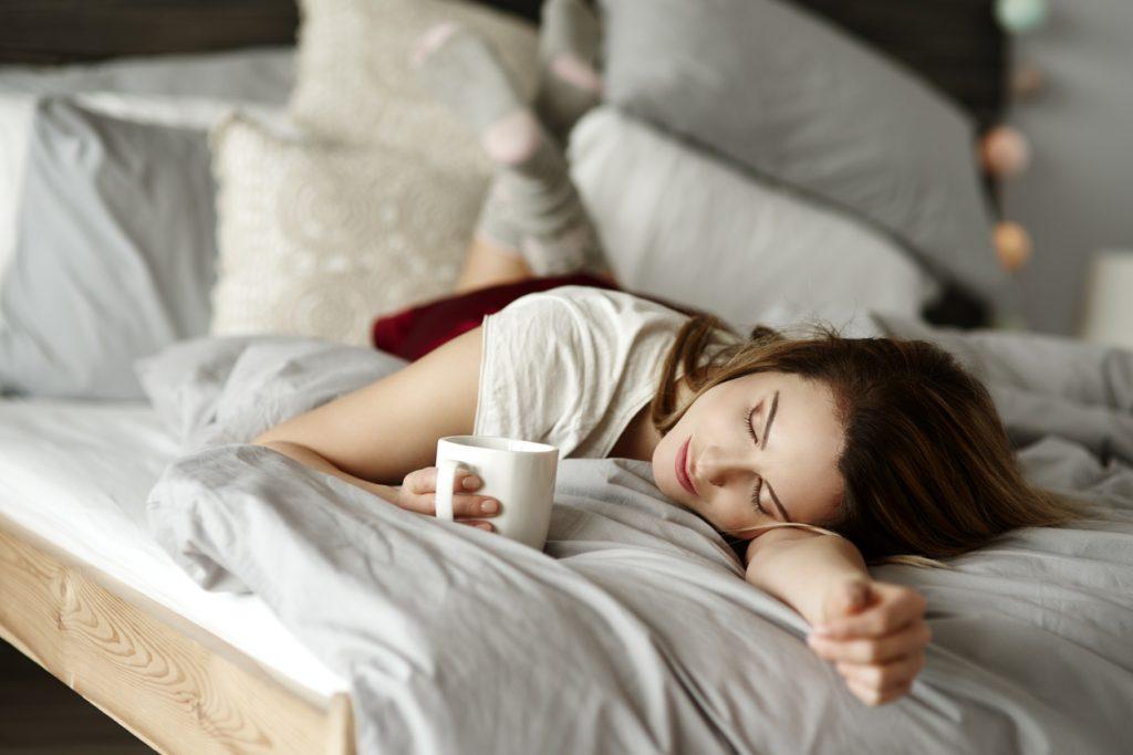 Vrouw drinkt thee om van in slaap te vallen