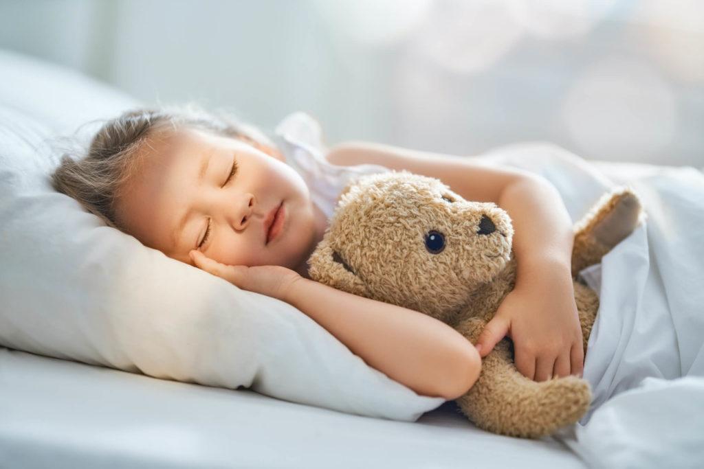 Kind slaapt met teddy beer